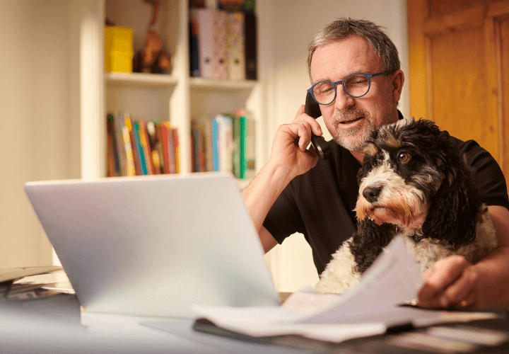 Man sat at laptop with dog by is side